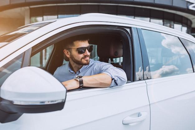 Hübscher geschäftsmann, der in ein auto reist