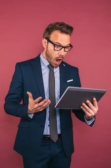 Hübscher geschäftsmann, der in einer tablette arbeitet