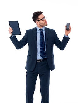 Hübscher geschäftsmann, der in seinen händen digitales tablett und handy hält
