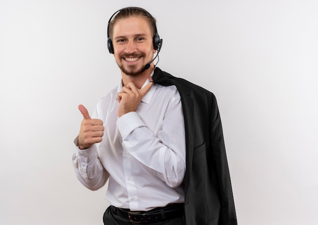 Hübscher geschäftsmann, der jacke über schulter mit kopfhörern mit einem lächelnden mikrofon hält, das daumen oben zeigt, die über weißem hintergrund stehen