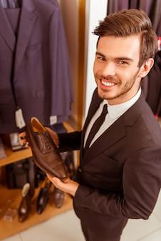 Hübscher geschäftsmann, der klassische schuhe lächelt und hält.