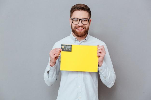 Hübscher geschäftsmann, der leeres papier und debitkarte hält