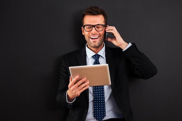 Hübscher geschäftsmann, der mit handy und digitalem tablet arbeitet