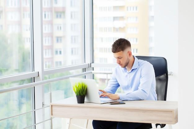 Hübscher geschäftsmann, der mit laptop im büro arbeitet.
