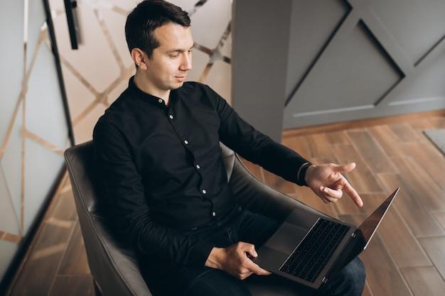 Hübscher geschäftsmann, der mit tablette im büro arbeitet