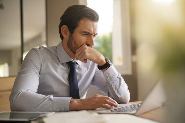 Hübscher geschäftsmann, der schwer an laptop im modernen büro arbeitet