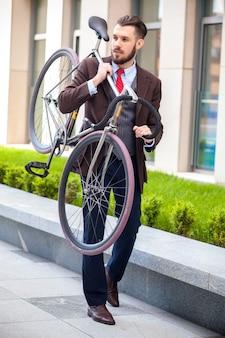 Hübscher geschäftsmann, der sein fahrrad auf stadtstraßen trägt. das konzept des modernen lebensstils junger männer