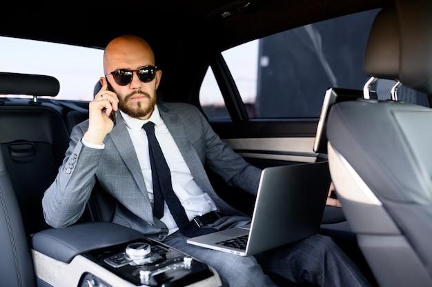 Hübscher geschäftsmann, der sein handy in einem modernen auto mit einem fahrer im zentrum der stadt benutzt. geschäftskonzept