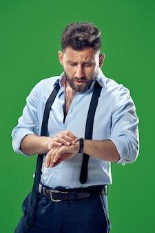 Hübscher geschäftsmann, der seine armbanduhr lokalisiert auf grünem hintergrund prüft. attraktives männliches halbes länge vorderes porträt