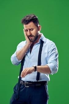 Hübscher geschäftsmann, der seine armbanduhr lokalisiert auf grünem hintergrund prüft.