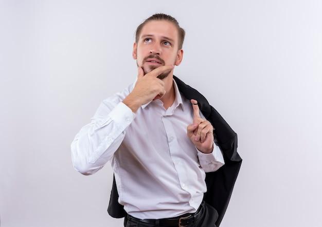 Hübscher geschäftsmann, der seine jacke auf schulter trägt, die beiseite mit nachdenklichem ausdruck auf gesicht denkt, das über weißem hintergrund steht