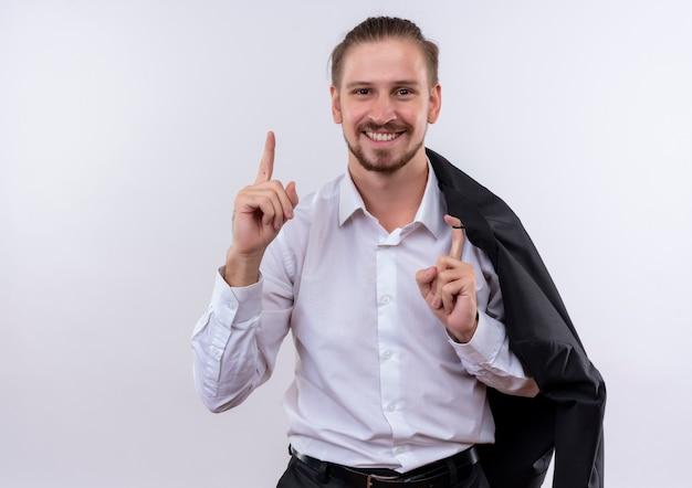 Hübscher geschäftsmann, der seine jacke auf schulter trägt, die kamera betrachtet, die mit glücklichem gesicht lächelt, zeigefinger zeigt, der neue idee über weißem hintergrund steht