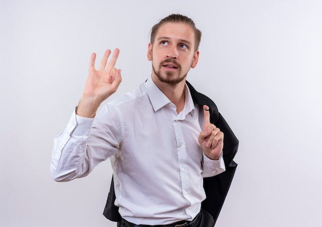 Hübscher geschäftsmann, der seine jacke auf schulter trägt, die lächelnd beiseite zeigt und ok zeichen steht über weißem hintergrund