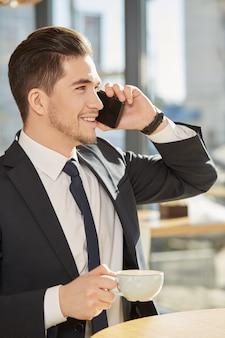 Hübscher geschäftsmann, der seinen kaffee spricht am telefon glücklich lächelt genießt