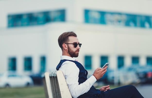 Hübscher geschäftsmann, der smartphone hält