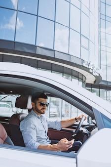 Hübscher geschäftsmann, der telefon im auto verwendet