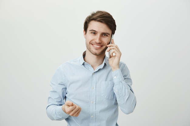 Hübscher geschäftsmann, der während des telefongesprächs gestikuliert