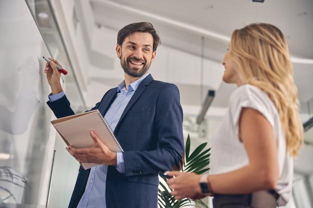Hübscher geschäftsmann, der weibliche kollegin anschaut und beim schreiben auf whiteboard lächelt