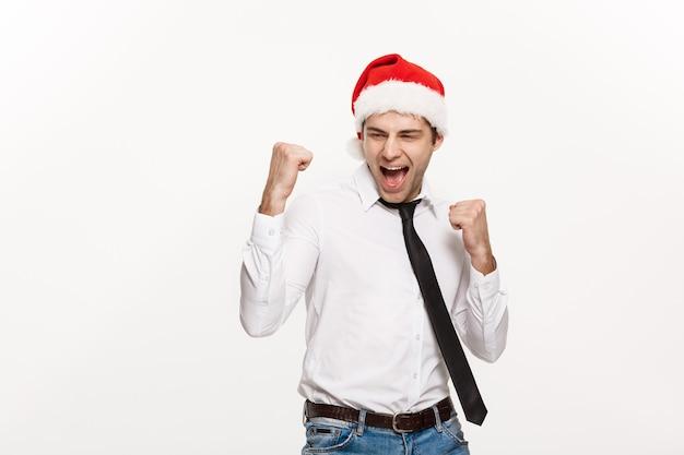 Hübscher geschäftsmann, der weihnachtsmütze trägt, die mit überraschendem gesichtsausdruck auf weiß aufwirft.
