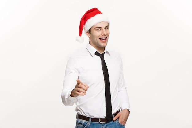 Hübscher geschäftsmann, der weihnachtsmütze zeigt finger auf weiß zeigt.