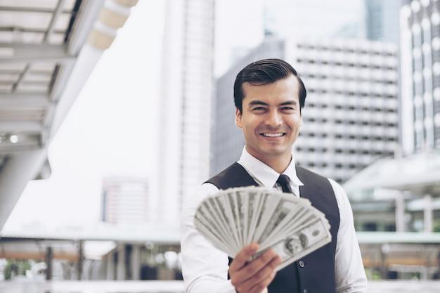 Hübscher geschäftsmann des glücklichen gesichtes, der geld us-dollar rechnungen auf geschäftsgebiet städtisch hält