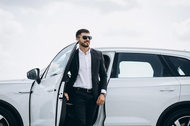 Hübscher geschäftsmann durch das weiße auto