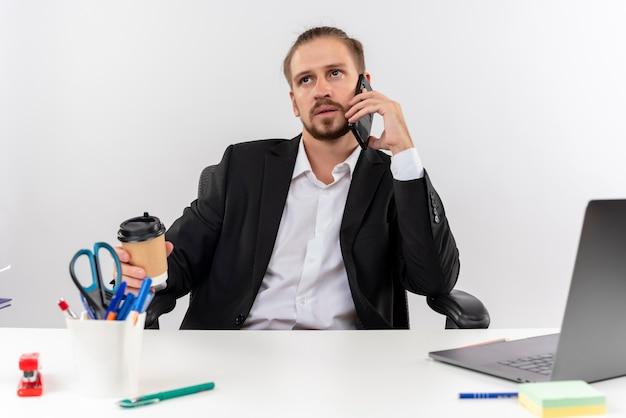 Hübscher geschäftsmann im anzug, der an laptop arbeitet, der auf handy spricht, das mit ernstem gesicht beiseite schaut, das am tisch in offise über weißem hintergrund sitzt