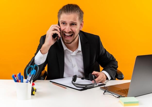 Hübscher geschäftsmann im anzug, der auf laptop arbeitet, der verwirrt und unzufrieden am tisch in offise über orange hintergrund sitzt