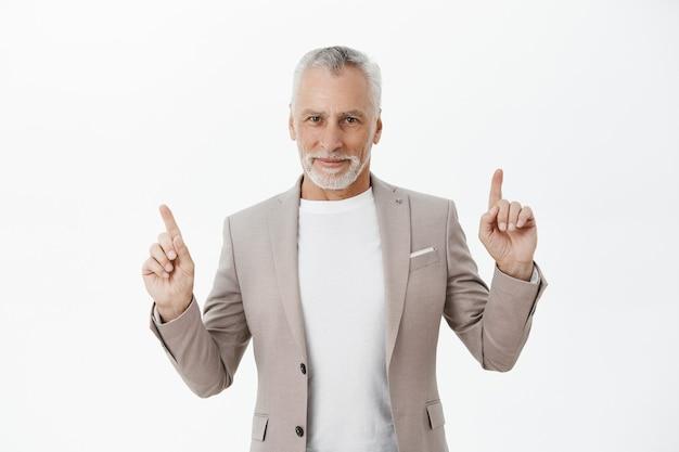 Hübscher geschäftsmann im anzug, der finger nach oben zeigt und erfreut lächelt