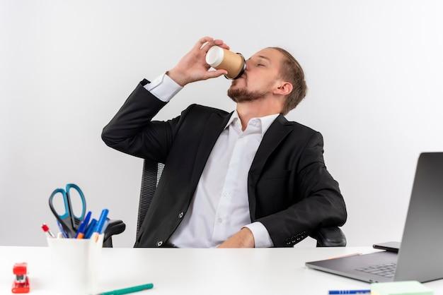 Hübscher geschäftsmann im anzug, der kaffee trinkt, der am tisch in offise über weißem hintergrund sitzt