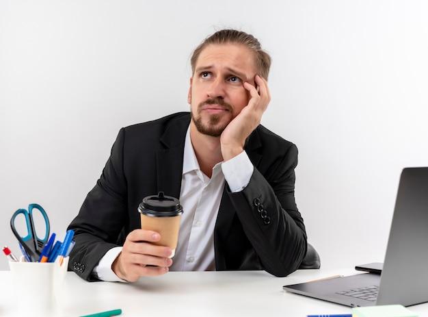 Hübscher geschäftsmann im anzug, der kaffeetasse hält, die auf laptop arbeitet, der müde und gelangweilt sitzt, die am tisch in offise über weißem hintergrund sitzen