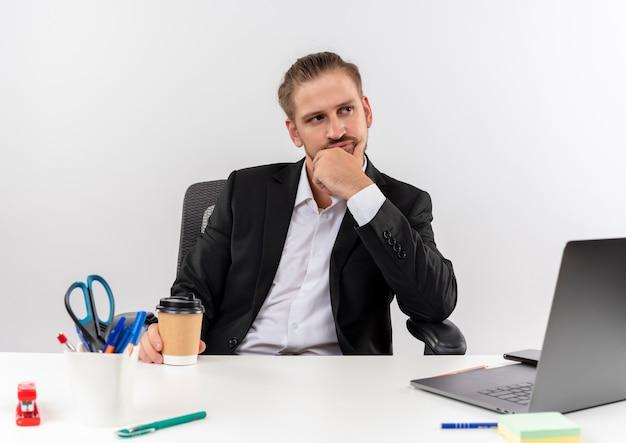 Hübscher geschäftsmann im anzug mit kaffeetasse, die seitlich verwirrt am tisch in offise über weißem hintergrund sitzt