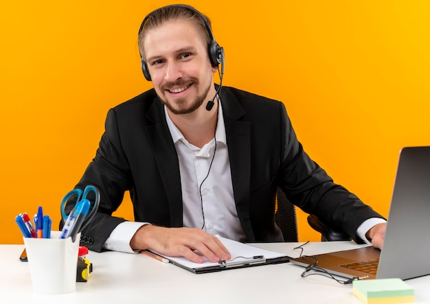 Hübscher geschäftsmann im anzug und in den kopfhörern mit einem mikrofon, das an einem laptop arbeitet, der kamera betrachtet lächelnd sitzt am tisch in offise über orange hintergrund