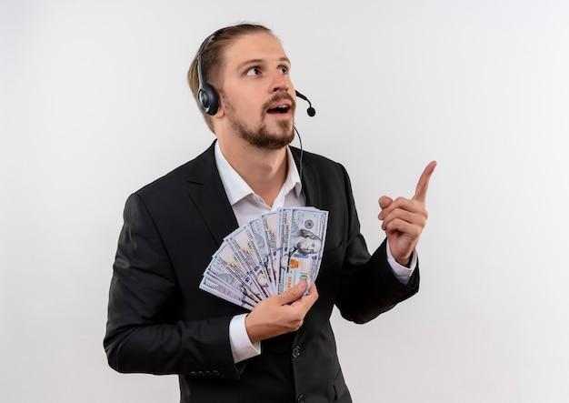 Hübscher geschäftsmann im anzug und in den kopfhörern mit einem mikrofon, das bargeld hält, das oben mit dem zeigefinger überrascht steht, der über weißem hintergrund steht