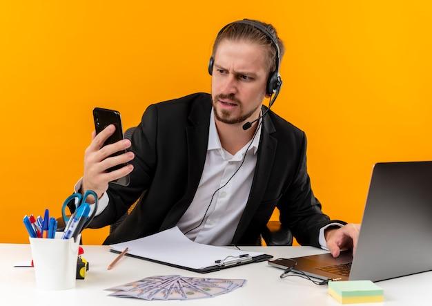 Hübscher geschäftsmann im anzug und in den kopfhörern mit einem mikrofon, das bildschirm seines smartphones mit ernstem gesicht betrachtet, das am tisch in offise über orange hintergrund sitzt