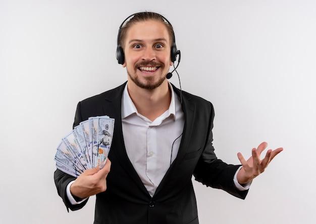 Hübscher geschäftsmann im anzug und in den kopfhörern mit einem mikrofon, das kamera betrachtet, die bargeld glücklich und aufgeregt über weißem hintergrund stehend zeigt