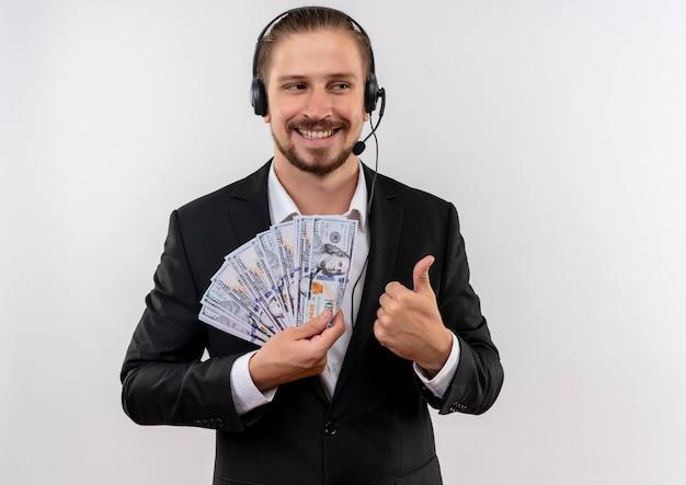 Hübscher geschäftsmann im anzug und in den kopfhörern mit einem mikrofon, das kamera betrachtet, die bargeld lächelt, das fröhlich daumen hoch zeigt, die über weißem hintergrund stehen