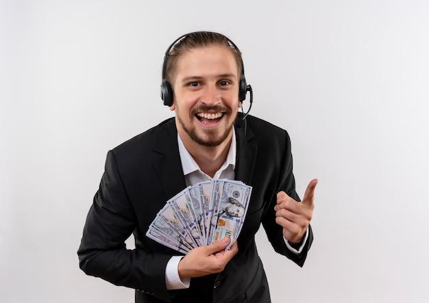 Hübscher geschäftsmann im anzug und in den kopfhörern mit einem mikrofon, das kamera betrachtet, die bargeld zeigt, das fröhlich über weißem hintergrund steht