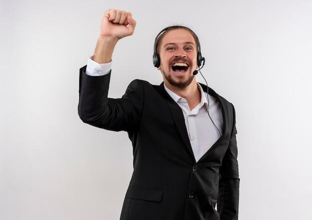 Hübscher geschäftsmann im anzug und in den kopfhörern mit einem mikrofon, das kamera betrachtet, die faust glücklich und aufgeregt über weißem hintergrund zusammenpresst