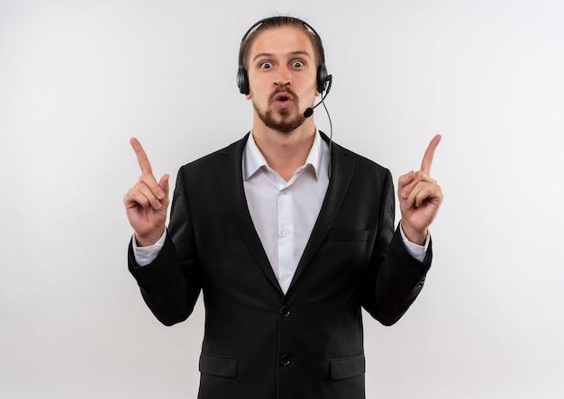 Hübscher geschäftsmann im anzug und in den kopfhörern mit einem mikrofon, das kamera betrachtet, die oben mit zeigefingern zeigt, überrascht und glücklich, über weißem hintergrund stehend