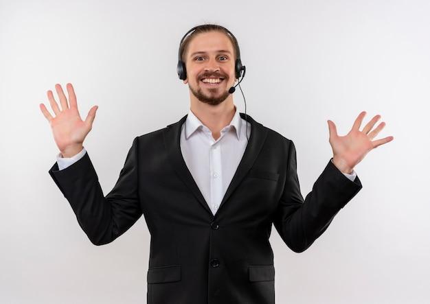 Hübscher geschäftsmann im anzug und in den kopfhörern mit einem mikrofon, das kamera betrachtet, die palmen in der übergabe über weißem hintergrund erhebt