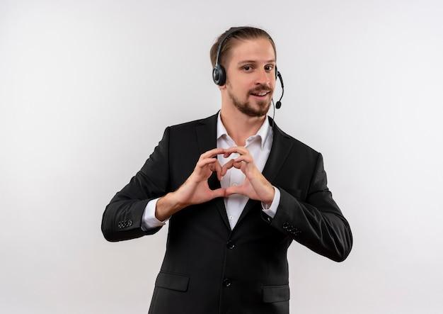 Hübscher geschäftsmann im anzug und in den kopfhörern mit einem mikrofon, das kamera betrachtet heratgeste mit den fingern über der brust lächelnd steht über weißem hintergrund