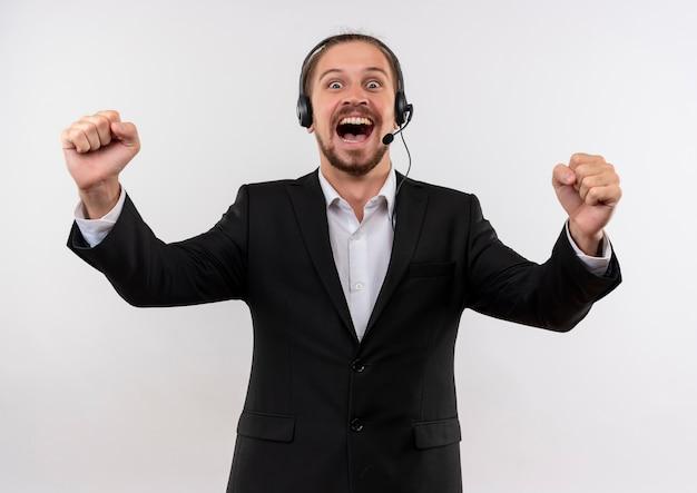 Hübscher geschäftsmann im anzug und in den kopfhörern mit einem mikrofon, das kamera-geballte fäuste verrückt glücklich über weißem hintergrund stehend betrachtet
