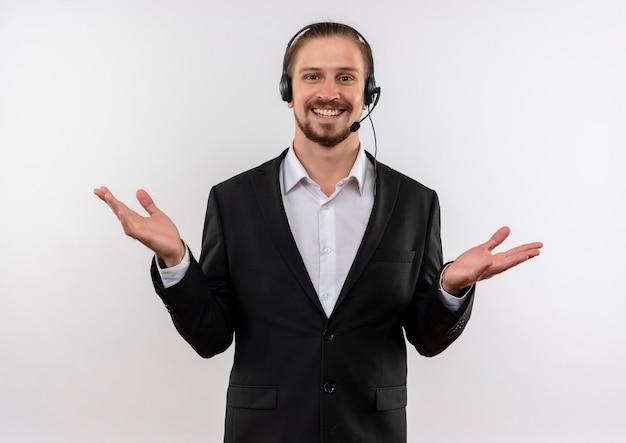 Hübscher geschäftsmann im anzug und in den kopfhörern mit einem mikrofon, das kamera glücklich und positiv lächelnd betrachtet, das fröhlich über weißem hintergrund steht