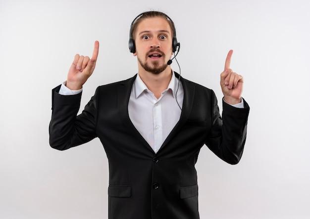 Hübscher geschäftsmann im anzug und in den kopfhörern mit einem mikrofon, das kamera glücklich und positiv zeigt, mit zeigefingern oben steht über weißem hintergrund