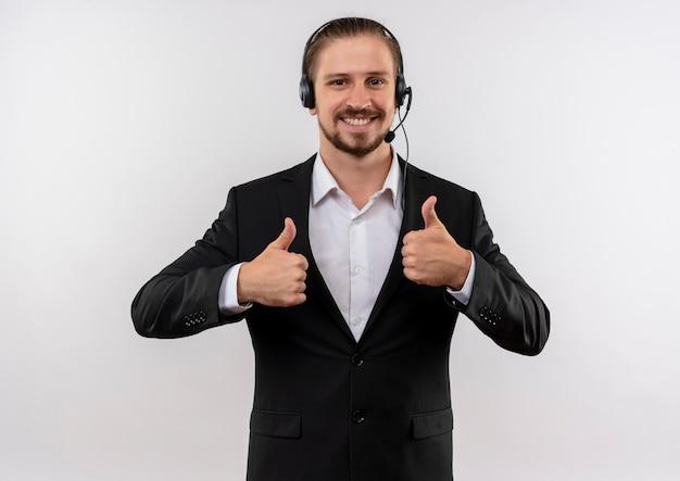 Hübscher geschäftsmann im anzug und in den kopfhörern mit einem mikrofon, das kamera lächelnd betrachtet, zeigt daumen hoch, die über weißem hintergrund stehen