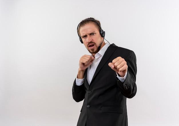 Hübscher geschäftsmann im anzug und in den kopfhörern mit einem mikrofon, das kamera mit ernstem gesicht betrachtet, das wie ein boxer aufstellt, der über weißem hintergrund steht