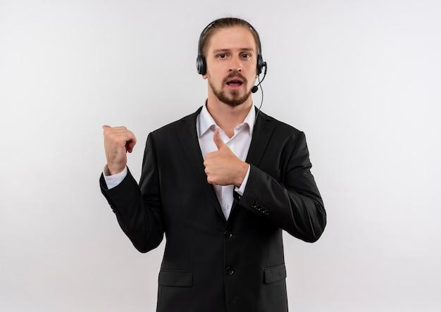 Hübscher geschäftsmann im anzug und in den kopfhörern mit einem mikrofon, das kamera positiv und glücklich zeigt, zeigt mit den fingern auf die seite, die über weißem hintergrund steht