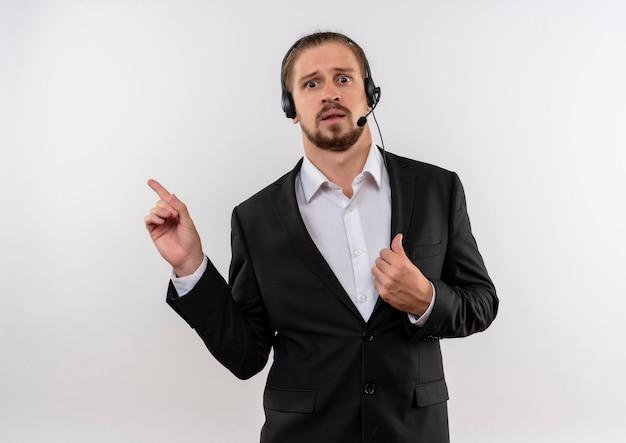Hübscher geschäftsmann im anzug und in den kopfhörern mit einem mikrofon, das kamera verwirrt betrachtet, zeigt mit den fingern auf die seite, die über weißem hintergrund steht
