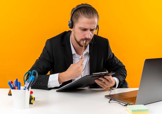 Hübscher geschäftsmann im anzug und in den kopfhörern mit einem mikrofon, das klemmbrett mit dokumenten hält, die mit ernstem gesicht schauen, das am tisch in offise über orange hintergrund sitzt